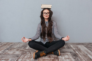 Young cute Asian woman meditating on the floor with books on the head as well as with eyes closed. Isolated gray background