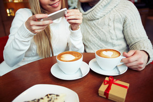 Young dates in sweaters photographing cappuccino while sitting in cafe
