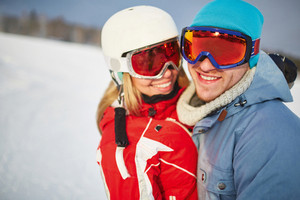 Young dates in winter sportswear and goggles looking at camera in natural environment