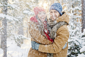 Young dates in winterwear enjoying snowfall