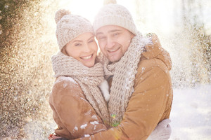 Young dates in winterwear looking at camera in snowfall