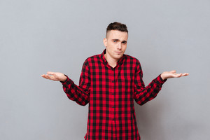 Young displeased man in shirt making displeased gesture and looking at camera. Isolated gray background