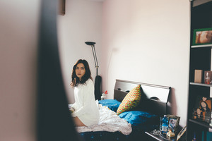Young eastern beautiful woman sitting on her bed, overlooking pensive -  serious, worried, thinking cocnept