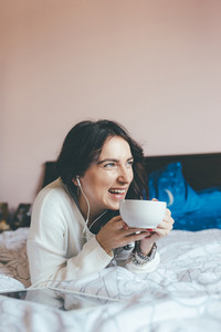 Young eastern woman lying on bed at home relaxing in her bedroom drinking coffee or tea listening music with earphones- relaxing, serene concept