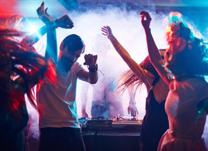 Young energetic people dancing by turntables of dj