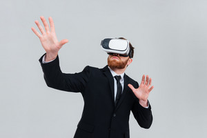 Young engineer in black suit wearing virtual reality device. Isolated gray background