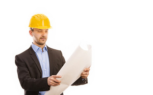 Young engineer with yellow helmet is isolated on white background.