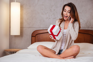 Young excited woman holding gift box and talking on mobile phone while sitting on bed