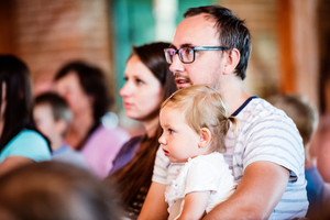 Young family with little daughter sitting outside in a crowd of people, watching show for children