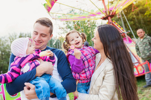 Young family with little girls enjoying time at fun fair, baby eating roll, girl with popsicle, amusement park