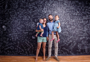 Young family with two little daughters against big blackboard with formulas and mathematical symbols