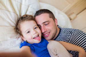 Young father and daughter lying in parents bed, taking selfie, sticking tongue out