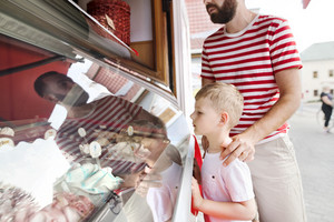 Young father and his little son buying ice cream. Sunny summer day.