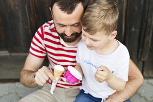 Young father and his little son eating ice cream. Sunny summer day.
