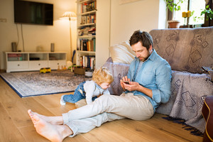 Young father at home, holding smart phone, texting, his cute little son playing around him
