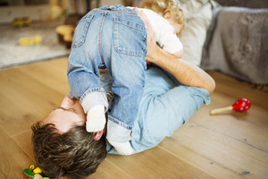 Young father at home lying on wooden floor playing with his little son, cuddling him.