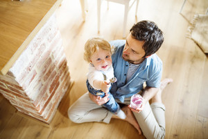 Young father at home sitting on the floor feeding his cute little son with yoghurt.