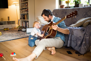 Young father at home sitting on wooden floor, his cute little son playing guitar that he is holding.