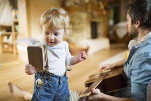 Young father at home sitting on wooden floor, playing guitar, his cute little son holding smart phone, playing with it.