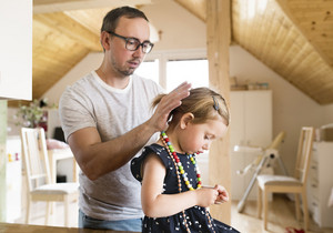 Young father at home with his cute little daughter making her a hairstyle.