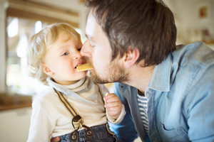 Young father at home with his cute little son eating biscuit together.