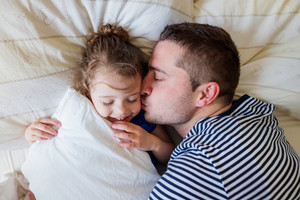 Young father having fun with his cute little daughter, lying in bed, kissing her
