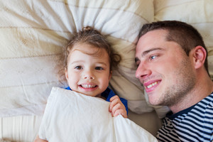 Young father having fun with his cute little daughter, lying in bed