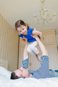Young father having fun with his cute little daughter, lying on bed, lifting her up in the air.