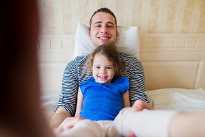 Young father having fun with his cute little daughter, sitting in bed