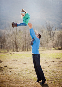 Young father having fun with his little daughter are having fun in autumn nature