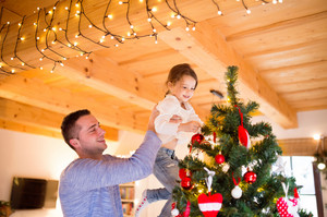 Young father holding his little daughter in his arms at home decorating Christmas tree together.