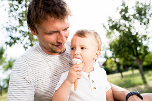 Young father holding his little son eating ice cream, sunny summer garden