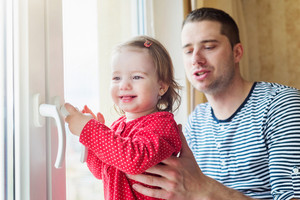 Young father in striped t-shirt holding his little daughter, standing at the window