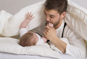 Young father is playing with baby in bed
