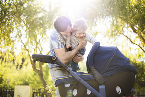 Young father outdoors in sunny summer park holding his cute little son in the arms looking at baby girl lying in stroller.