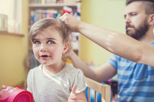 Young father styling hair of his daughter