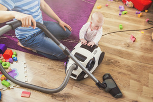Young father with his beautiful daughter hoovering floor