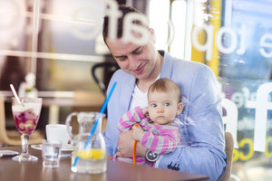 Young father with his cute baby daughter in cafe