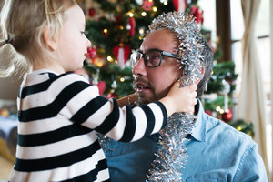 Young father with his cute little daughter decorating Christmas tree. Girl giving him silver tinsel garland around his head.