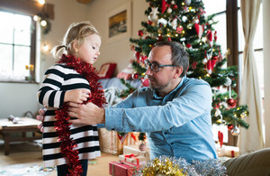 Young father with his cute little daughter decorating Christmas tree. Man wrapping red tinsel garland around the girl.