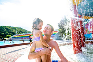 Young father with his daughter holding her in his arms in swimming pool in aqua park. Summer heat and water.