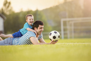 Young father with his little son having fun on football pitch