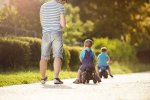 Young father with his little sons on motorbikes in green sunny park