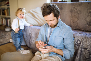 Young father with his son at home texting on sartphone.