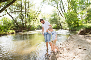 Young father with little boy at the river having fun, entering into the water, sunny spring day.