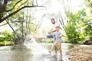 Young father with little boy in the river kicking water, having fun, sunny spring day.