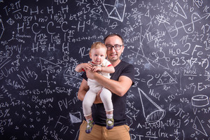 Young father with little daughter against big blackboard with formulas and mathematical symbols