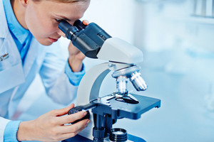 Young female chemist looking in microscope in lab