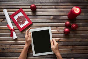 Young female hands with touchpad surrounded by Christmas symbols