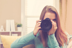 Young female photographer using a DSLR camera